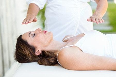 40334178 - calm woman receiving reiki treatment in the health spa