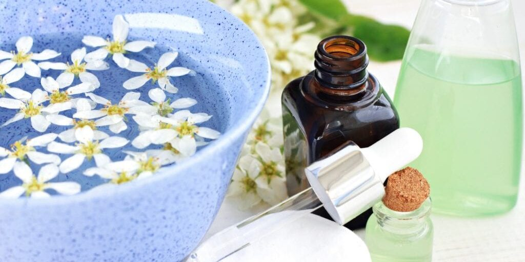 Herbal aromatherapy spa setting. Blue bowl of flower water, essential oil in dropper bottle, facial toner.
